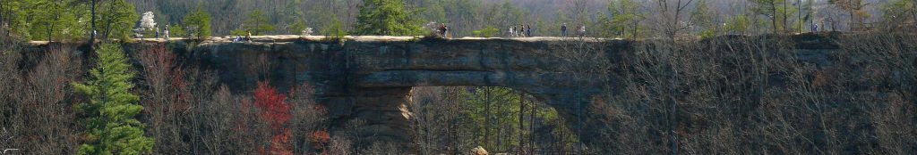 The natural bridge is a kentucky national park. Here we see from a distance a number of people crossing the rock structure. A truly natural bridge.
